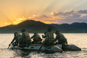 Special forces men in camouflage uniforms paddling army kayak. Boat moving across the river in the morning, diversionary mission,copy space. - Image