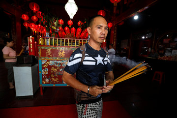 A man carries incense sticks as he prays during celebrations of the Chinese Lunar New Year of the Pig at a temple in Jakarta
