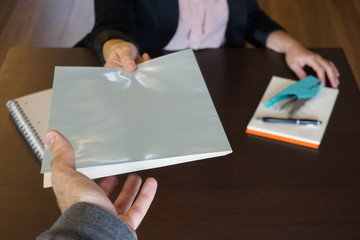 Woman is handing over a white file in direction camera while sitting at the desk in the office.