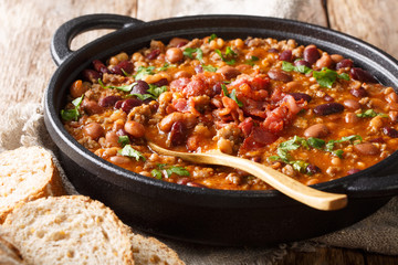 Delicious cowboy stew of beans with ground beef, bacon in a spicy sauce closeup in a bowl. horizontal