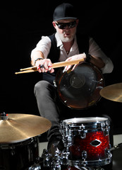 Drummer with a drumsticks in his hands sits behind drum kit on the black background