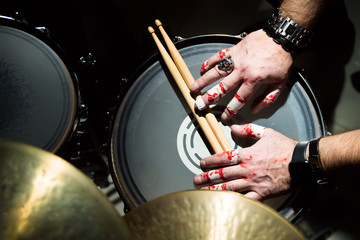 Hands of a musician with drumsticks lie on the drum