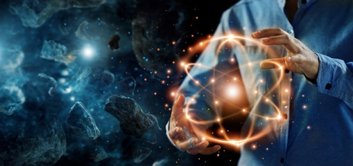 .Abstract science, hands holding atomic particle, nuclear energy imagery and network connection on meteorites space planets background.