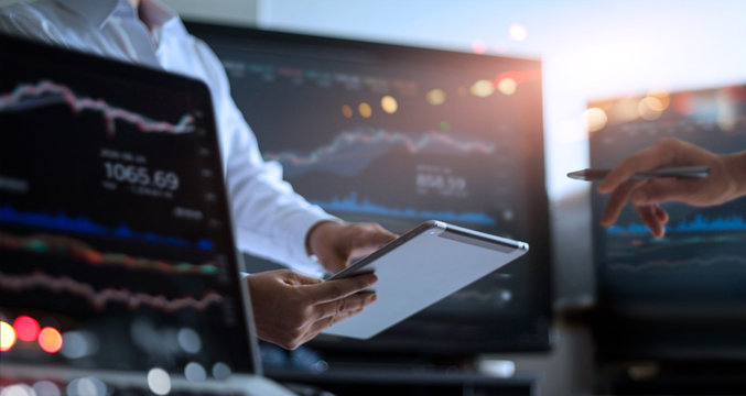 Business team working together. Businessman using tablet for analyzing data stock market in monitoring room with team pointing on the data presented in the chart, financial investment concept.