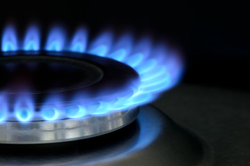 Natural gas burning on kitchen gas stove on black