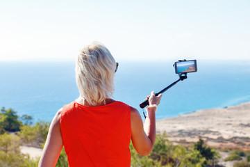 Woman take photo of Mediterranean Sea. Happy woman travel Cyprus.
