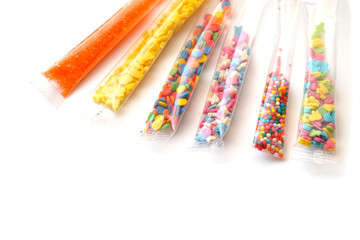 Isolated set of bright confectionery toppings in six small transparent packages on a white background