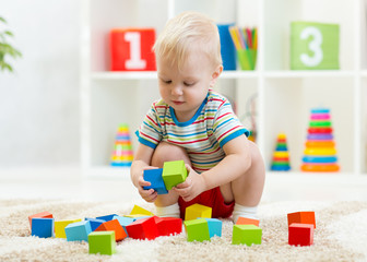 child toddler playing wooden toys at home or nursery