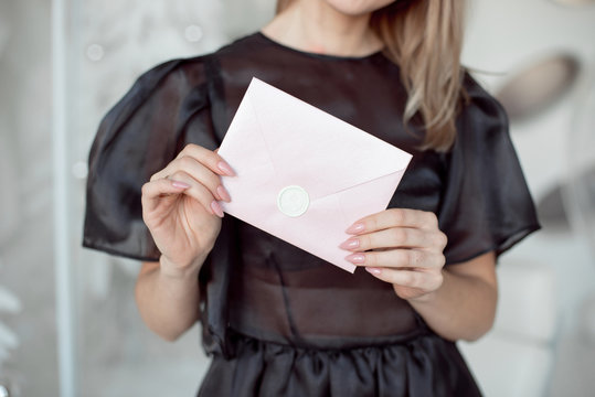close-up photo of a female hands holding a pink invitation envelope with a wax seal, a gift certificate, a card, a wedding invitation card