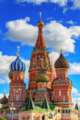 Architecture of St. Basil's Cathedral in sunny day on a background of blue sky with white clouds