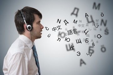 Young man with headphones is learning different foreign languages.
