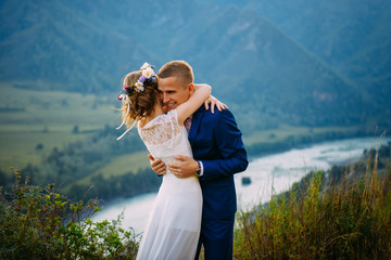 Happy newlywed couple hugging on top of the rock with background of mountains