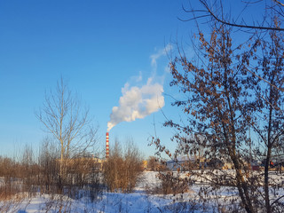 factory pipes with smoke in cold winter landscape. Pipes with smoke. Energy industry concept.