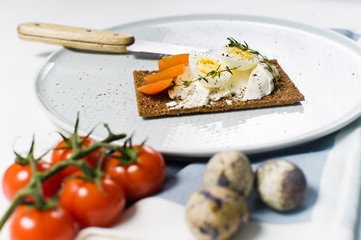 Quail egg toast. Ingredients tomatoes, egg, cheese, rye bread. White background, side view