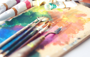 The artist's workplace: palette, brushes, tubes of oil paint and palette knife. Everything is illuminated by the sun.