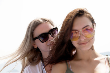 Two beautiful girls near the sea and mountains background