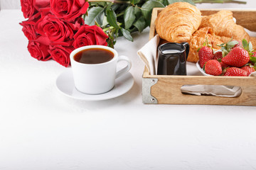 Cup of coffee and croissant on wooden tray. Festive breakfast with a bouquet of red roses on white table. Copy space.