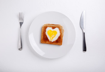 Toasted bread with fried eggs within on white plate. Heart Eggs. Festive breakfast on white table. Happy Valentines day. Top view.  Copy space.
