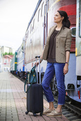 beautiful middle-aged woman with luggage rides in retro trip
