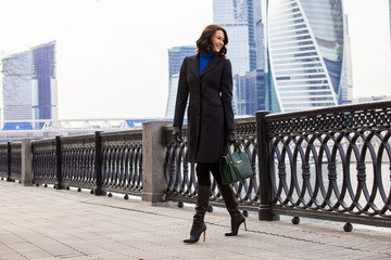 middle-aged woman in a fashionable dark coat and a green handbag walking on the promenade. copy space