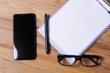 Working place on wooden table. Office desk table with eye glasses shot notepaper, pen and smartphone. Top view with copy space, flat lay