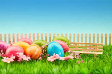 Ostereier im Garten zu Ostern neben Bank