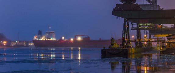 Fond de hotte en verre imprimé Port SEAPORT AT DAWN - The cargo ship maneuvers to transhipment wharf in Swinoujscie