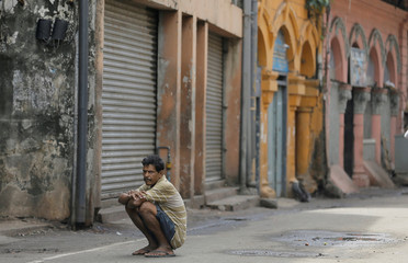 Labourer sits on a road near closed wholesale stalls during protest by Food Commodities Importers and Traders Association in Colombo