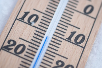 wooden thermometer in snow with freezing temperature macro