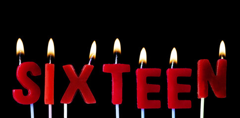 Sixteen spellt out in red birthday candles against a black background