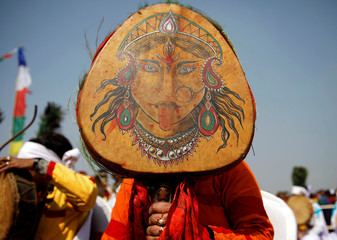 A Tamang shaman holds her drum with a picture of Goddess Maha Kali as she participates during the Sonam Lhosar in Kathmandu