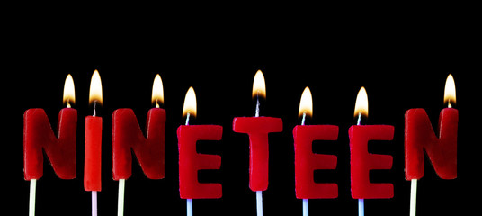 Nineteen spellt out in red birthday candles against a black background