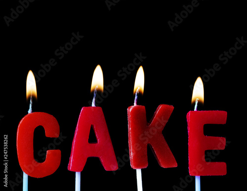 Cake Spellt Out In Red Birthday Candles Against A Black Background
