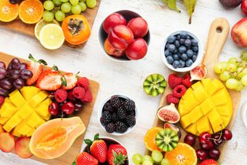 Wall Mural - Healthy breakfast, cut colorful rainbow fruits, strawberries raspberries oranges plums apples kiwis grapes blueberries mango persimmon, copy space, selective focus