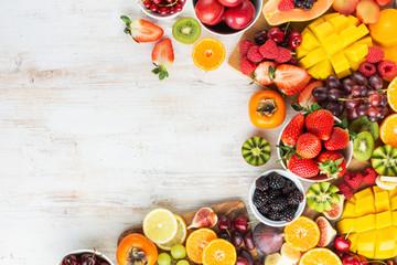 Wall Mural - Healthy raw fruits background, cut mango, strawberries raspberries oranges plums apples kiwis grapes blueberries cherries, on white table, copy space, top view, selective focus