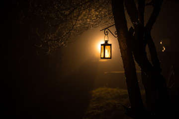 Beautiful colorful illuminated lamp in the garden in misty night. Retro style lantern at night outdoor.