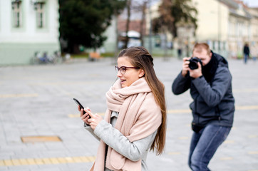 Photographer taking stock pictures of a young beautiful teenge girl using phone