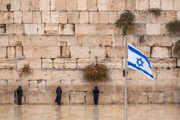 Israeli flag against the western wall  on a cloudy day