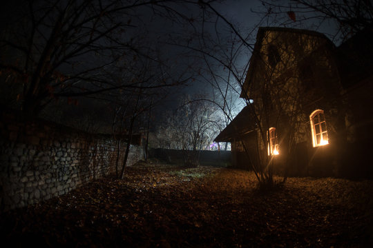 Old house with a Ghost in the forest at night or Abandoned Haunted Horror House in fog. Old mystic building in dead tree forest. Trees at night with moon.