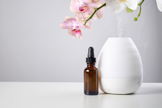 Oil diffuser with glass amber bottle and orchid flowers on white table