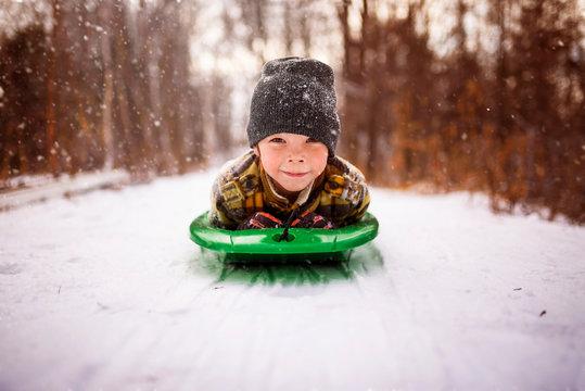 Boy lying on a sledge, Wisconsin, United States