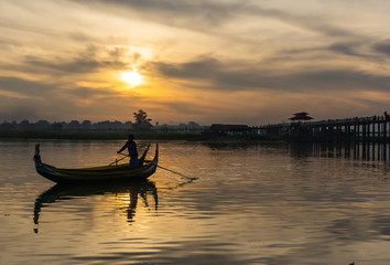 landscape with fisherman rowing fishing boat before sunrise near iconic U-Bein Bridge, the longest teak foot bridge crosses the shallow Lake Taungthamanin
