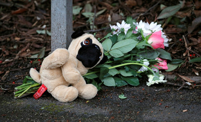 Soft toy and a bouquet of flowers are left at the scene of a house partly destroyed by a fire in Stafford
