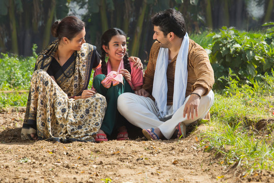 Happy and smiling rural family sitting in their agriculture field.