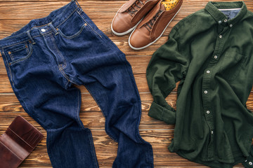 Top view of jeans, brown shoes and green shirt on wooden background