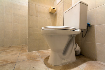 Interior of simple spacious empty bathroom equipment, white ceramic toilet lavatory on copy space background of light beige tile walls and floor. Comfortable home concept.