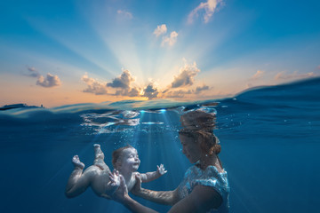 Baby infant with mother diving underwater under water line against sunset sea background