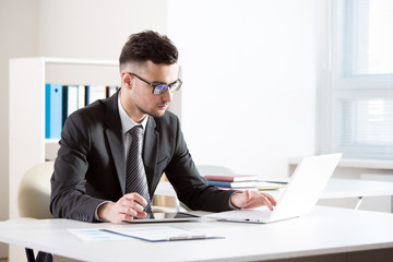 Young handsome businessman working in an office