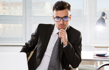 Serious confident businessman working in office