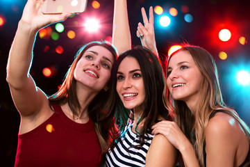 Smiling girls taking selfie in a night club
